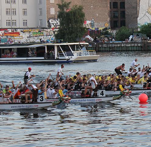 Gruppen fahren Drachenboot gegeneinander
