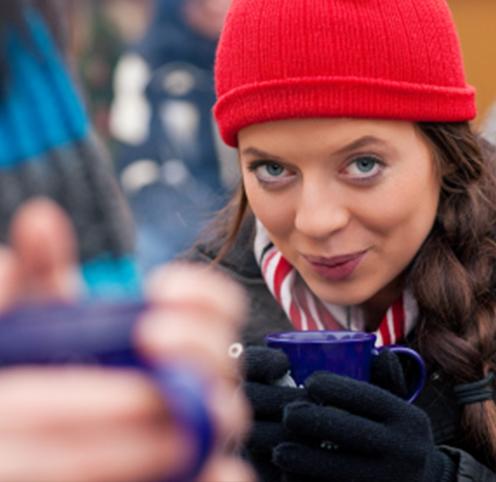 Junge Frau trinkt Glühwein auf der Weihnachtsfeier auf dem Weihnachtsmarkt